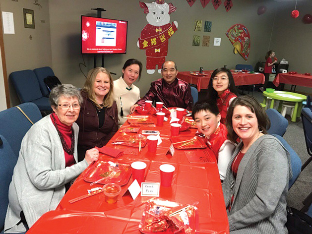 A family gathers around a table at Salem Lutheran Church's Chinese New Year celebration.