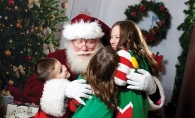 Santa hugs a group of children at a Custom One Charities event.