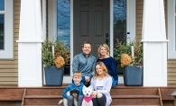 A family sits on their front steps in this photograph from the Front Steps Project