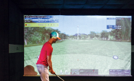 A golfer plays a virtual golf simulation at X-Golf in Woodbury.