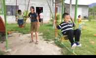 A volunteer with Woodbury nonprofit Milk and Honey Missions pushes children from the Honduran village of Villa San Antonio on a swing.