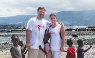Michael and Amy Lindahl spend some time with some local children as they help deliver fresh water with Healing Haiti.
