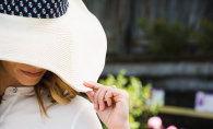 A woman practices healthy sun habits by shielding her face with a hat.