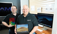 Team Technology shows off a Macbook with an iMac in the background.