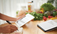 A person plans a healthy menu using a tablet and a notebook.