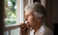 An elderly woman looks out a window.