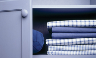 A pillow and sheets sit organized on shelves, ready for tidying up before a downsizing move.