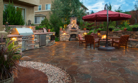 A beautiful outdoor space after a patio renovation, featuring a fireplace, grill, seating, brick floors and more.