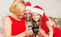 A mother, father and daughter review their family holiday photos