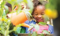 A child tends to a Garden Box at Woodbury YMCA.