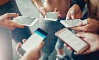 A group of people look at their phones, planning their weekly fitness routines.