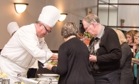 A chef prepares food for two guests at the Woodbury Community Foundation's Chef Fest.