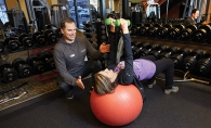 Jacek Kozdroj guides a client through an exercise at Anytime Fitness in Woodbury.