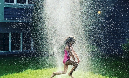 A girl jumps through a sprinkler in a Woodbury backyard.