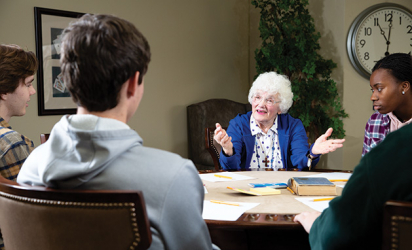 A senior citizen talks to three high schoolers at a table.