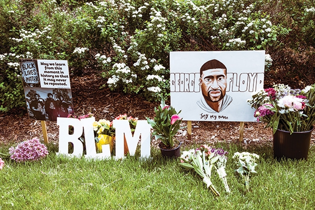 Signs and flowers ta a memorial for George Floyd.