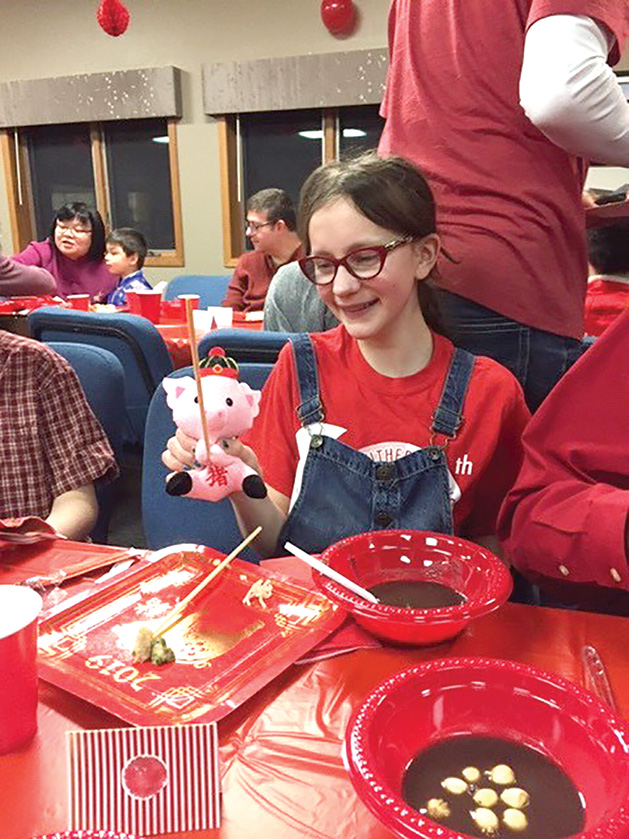 A child holds a doll at Salem Lutheran Church's Chinese New Year celebration.