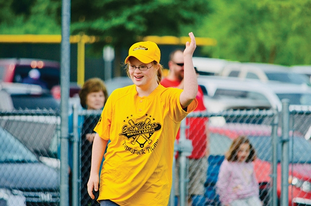 A girl raises her hand at an East Metro Miracle League game.