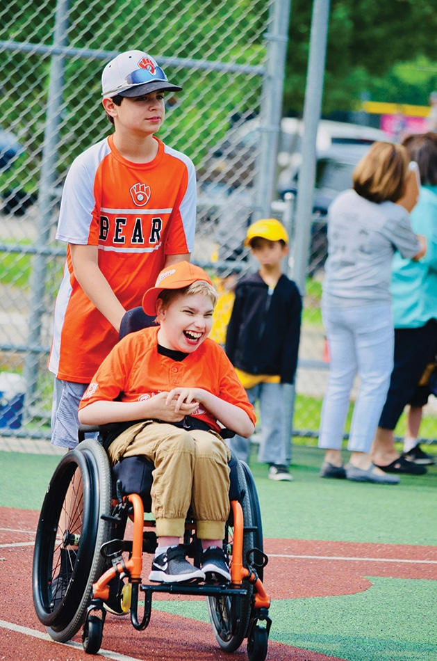 A boy pushes another boy in a wheelchair at an East Metro Miracle League game