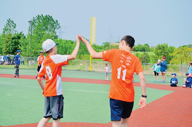 Two players high-five at an East Metro Miracle League game