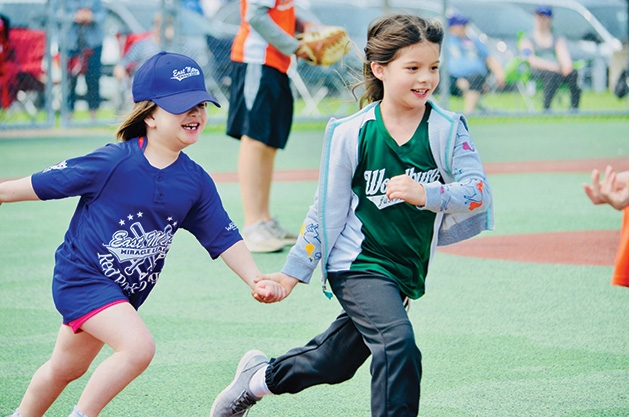 Two players run at an East Metro Miracle League game.