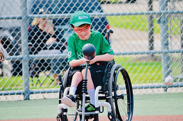 A player swings the bat at an East Metro Miracle League game
