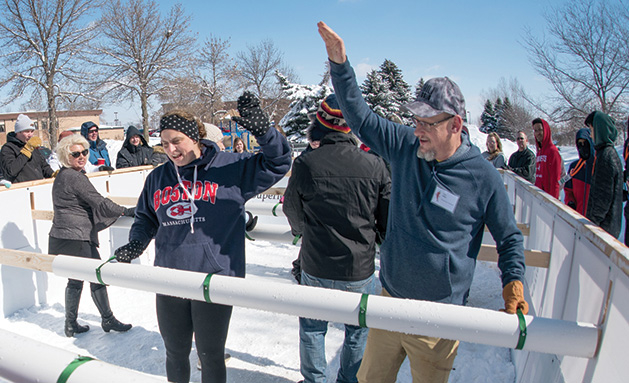 Two people high-five in an outdoor rink.