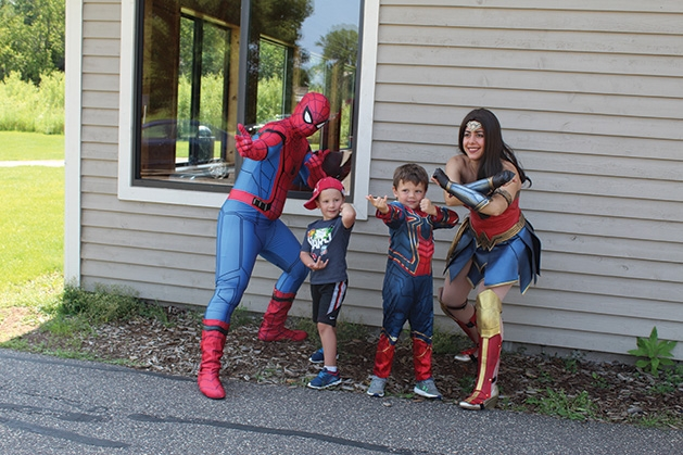 Kids pose with heroes at Woodbury Parks & Rec's Superhero Academy
