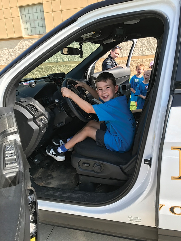 A child sits behind the wheel at Half Pint Safety Camp