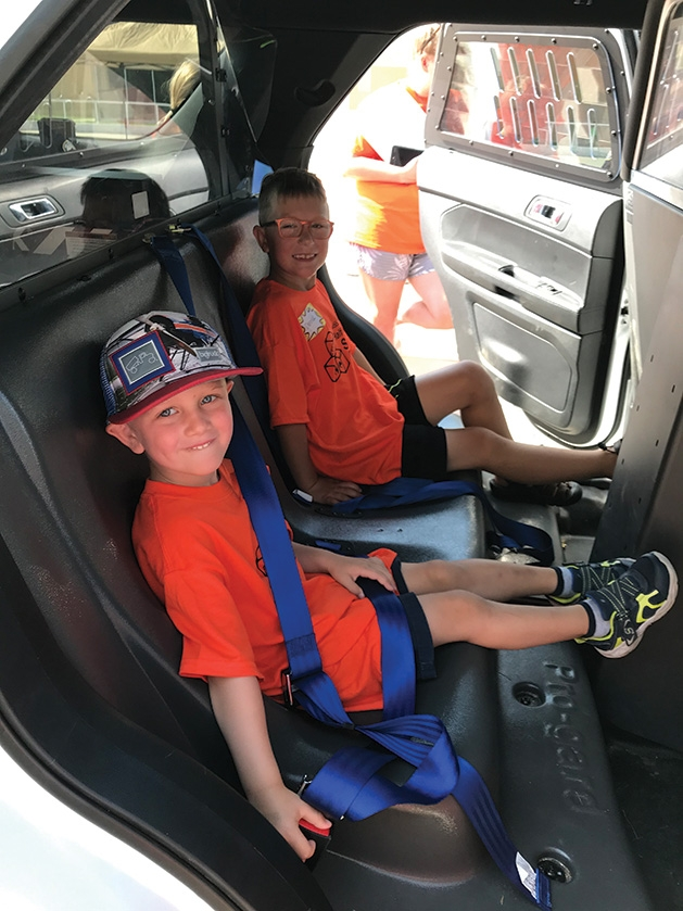 Kids sit in a car at Half Pint Safety Camp