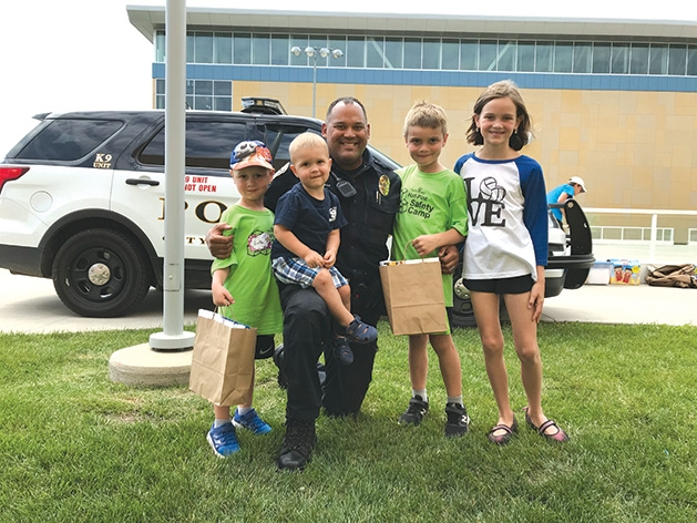 Kids pose with a police officer at Half Pint Safety Camp
