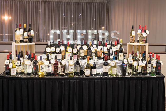 A table filled with wine and a light-up Cheers sign at the Woodbury Chamber Awards Gala.