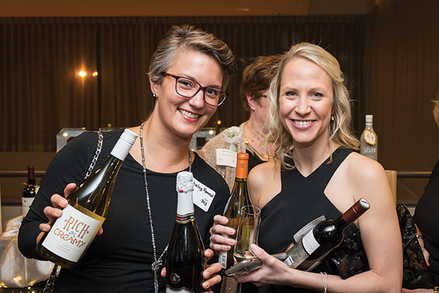 Two Woodbury Chamber Awards Gala attendees hold bottles of wine.