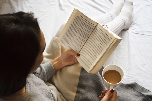 """A woman reads Erik Larson's """"The Strange Case of the Alchemist's Daughter"""" while drinking a cup of coffee."""