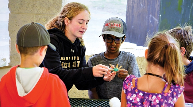 A camp counselor guides children through an activity at Camp Carver.