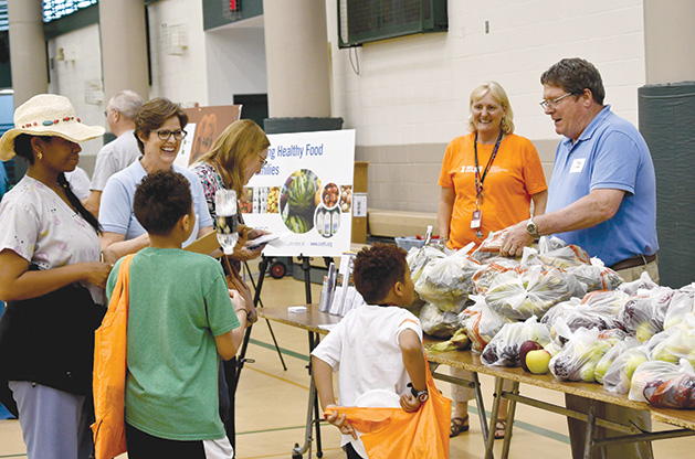Food shelf volunteers chat with families about healthy fruit and veggies at a local gathering.