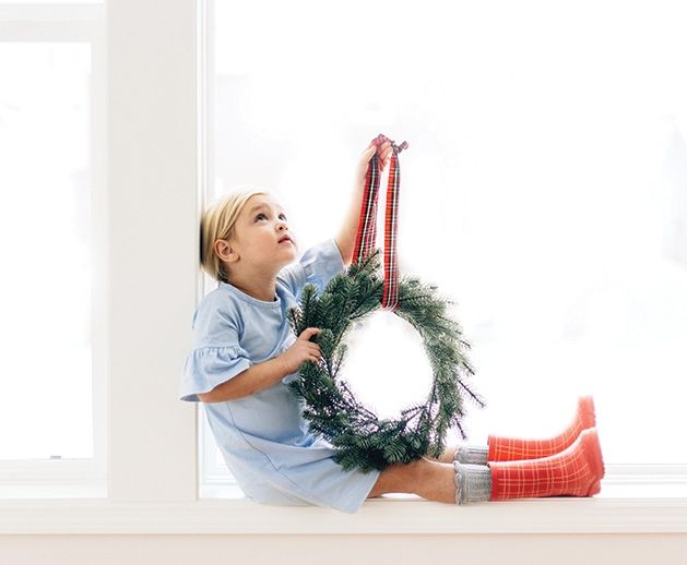 A child holds a wreath in this Focus on Woodbury photo contest winner.