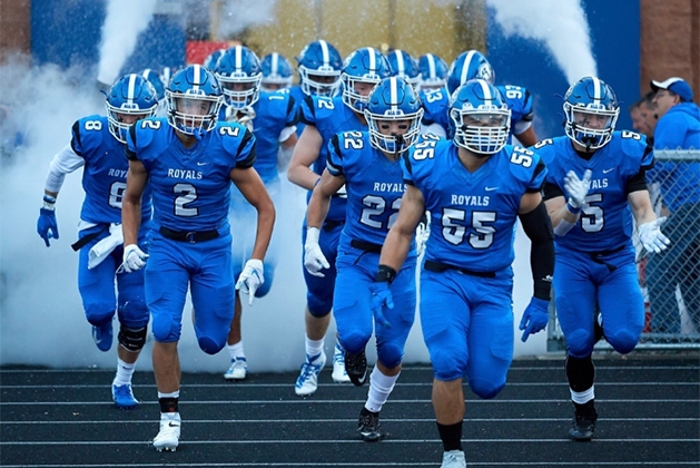 The Woodbury High School football team charges onto the field before a game.