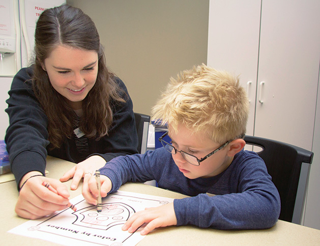 A Family Achievement Center therapist works with a young client.