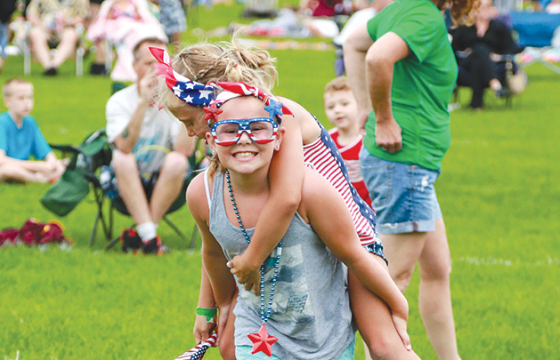 Two girls decked out in red, white and blue celebrate the Fourth of July at the Woodbury fireworks show.