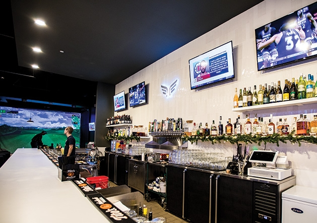 The bar at Birdi Golf, with a golf simulation station in the background.