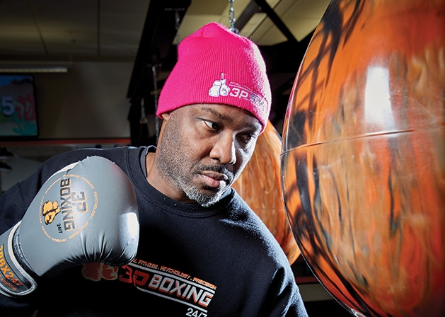 Mike Lewis, owner of 3P Boxing 24/7, punches a punching bag.