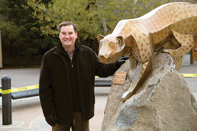 Eric Galler stands next to a statue of a leopard.