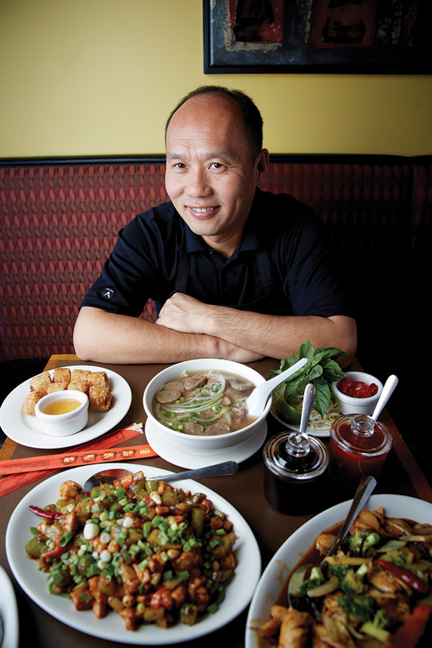 Duc's Restaurant owner Duke Kim sits in front of some of his food.