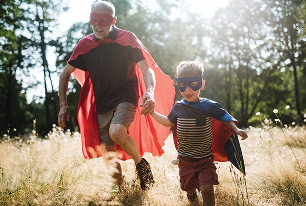 A grandfather and grandson play superheroes