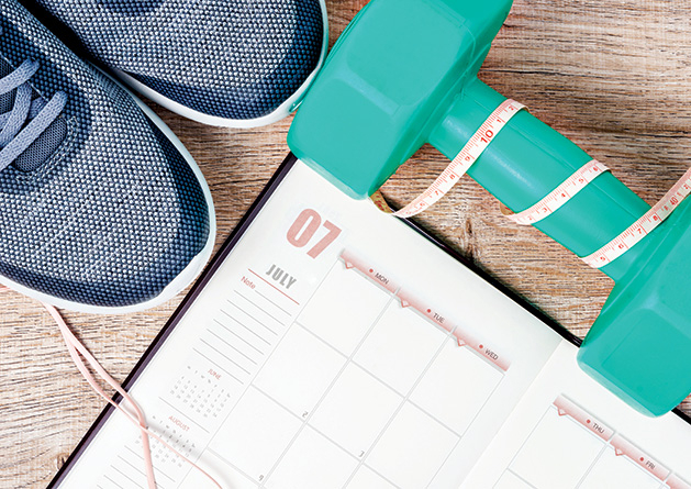 Exercise shoes, a free weight and a schedule tracking fitness goals.