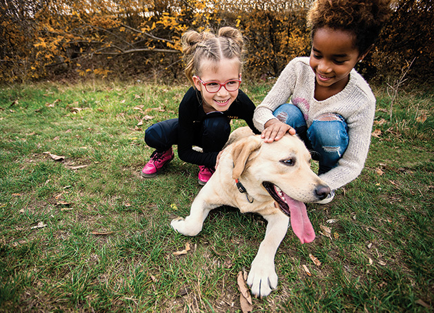 Two children play with a dog at Coco's Heart Dog Rescue Academy.