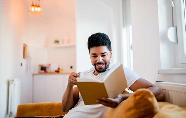 Man reading book at home in living room