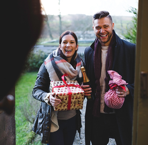 A couple brings wine and presents to a family Christmas gathering.