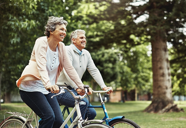 Two seniors on bikes, on their way to the East Twin Cities Boomers and Seniors Expo.